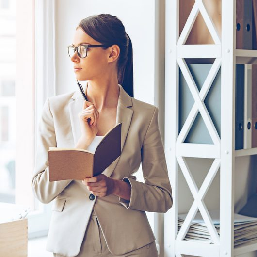 I need to make some changes! Pensive young beautiful businesswoman in glasses holding notebook and looking through window while standing at her working place