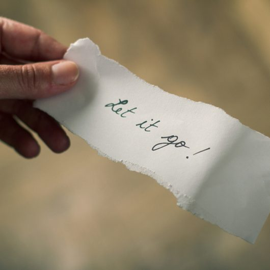 Hand holding a note of paper with the message let it go written on it