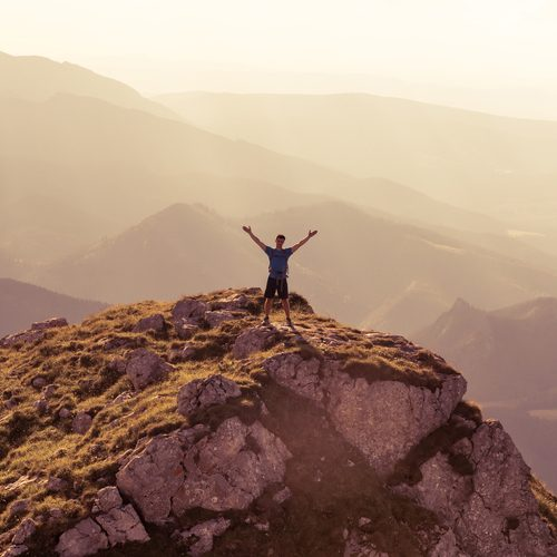 silhouette of successful man on the top of mountain. Concept of sport motivation inspiration