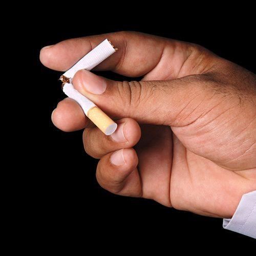 Mans hand breaking a cigarette