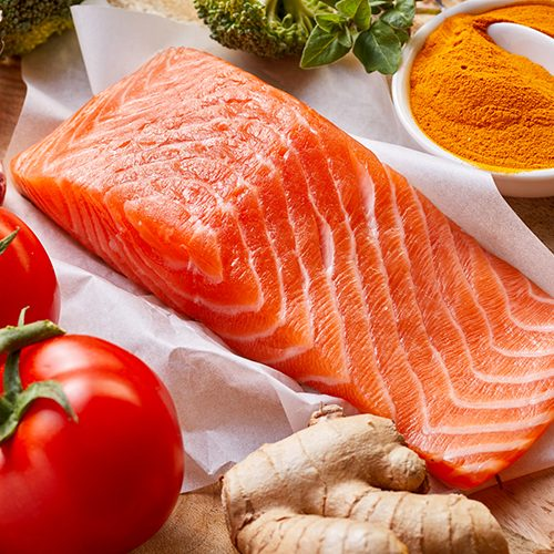 Nutrition for a healthy heart and cardiovascular system with fresh raw salmon rich in omega-3 fatty acids, tomatoes, turmeric, root ginger, stick cinnamon and garlic on a wooden table