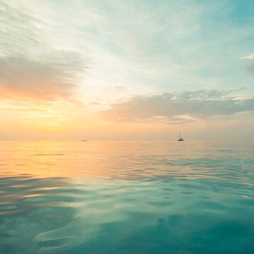 Look out on a calm blue sea with boat in the distance at sun rise