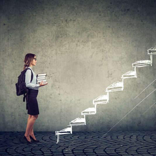 Female student with books standing on the stairs of education leading to success